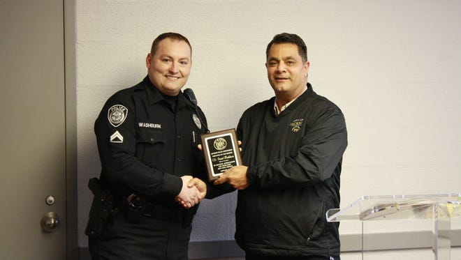 Jackson Police Department Officer Daniel Washburn stands with Deputy Chief Barry Michael after being named Employee of the Month.