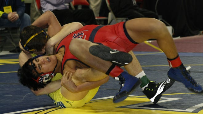 Livonia Franklin's Nathan Atienza, red, flips his opponent, River Shettler of Hartland during the MHSAA individual wrestling state championships on March 3, 2017, at the Palace of Auburn Hills.