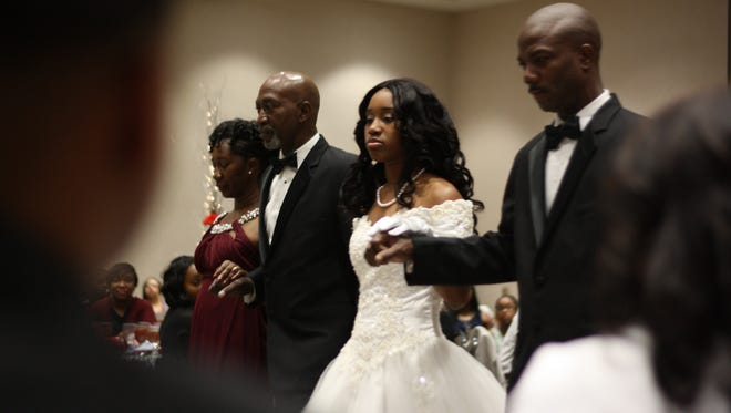Debutante Tatiyana DeMoss, center in white, is escorted to her chair by her grandfather Gilland DeMoss Sr., second from left, and parents Twainna and Lester Mack.