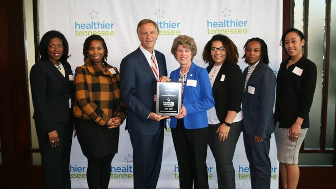Gov. Bill Haslam presents a plaque to Mayor McMillan and members of the Mayor's Fitness Council/Healthy Clarksville designating Clarksville as a Healthier Tennessee Community.