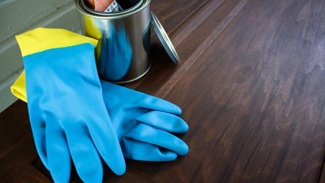 Rubber gloves and paintbrush used to refinish wood door
