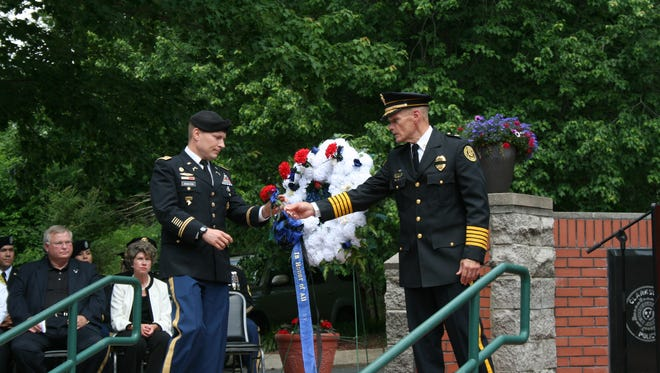 Clarksville Police Chief Al Ansley hands a flower to Army Lt. Col. Michael Johnston to place on a wreath that honors law enforcement from the city, county, state, county and military who died in the line of duty.