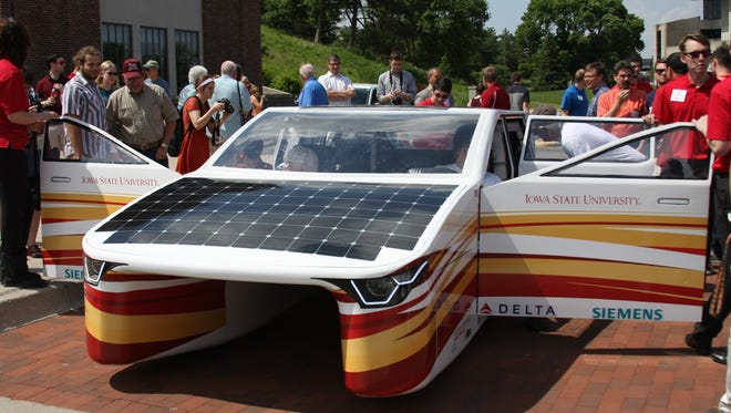 """Crowds gather at the unveiling of """"Penumbra,"""" the most recent project by Iowa State University's solar car team, PrISUm. The car will be stopping Friday, June 23, in Oxford."""