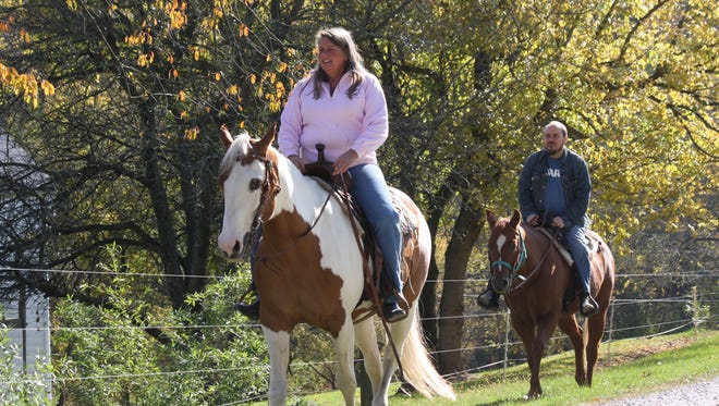 Misty Ridge Farm is one of the farms you can visit on the Campbell County Backroads Farm Tour on Saturday, July 17. Pictured: Misty Ridge Farm owner Anna Zinkhon, riding her horse Dixie, leads the way down for Eric Bates on a riding lesson at her Camp Springs farm.