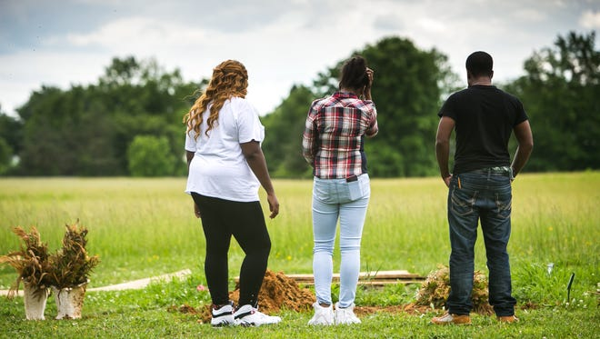 Tyzell Cephas, 23, is joined by his wife Takira Jones-Cephas (left) and cousin Laqueen McDuffie (center) as he visits the grave site of his 16-year-old sister Tynesia Cephas at Silverbrook Cemetery in Wilmington.