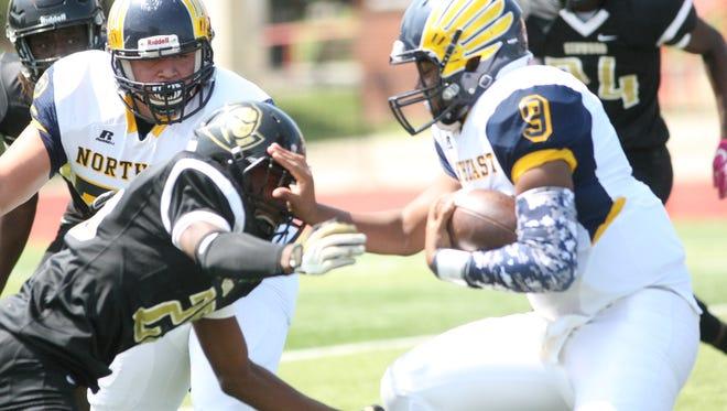 Northeast quarterback Heath Williams stiff-arms a Kenwood defender during their Region 7-5A game Saturday afternoon at Austin Peay's Fortera Stadium.