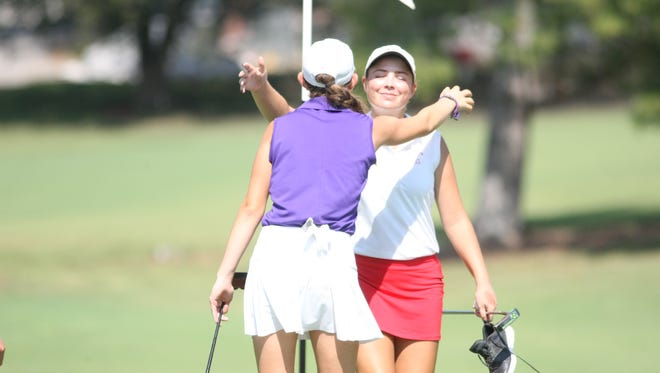 Rossview's Catherine Caudill hugs Clarksville High's McKinley Cunningham after the 18th green at the conclusion of the Region 5, Large School tournament Monday at Swan Lake.