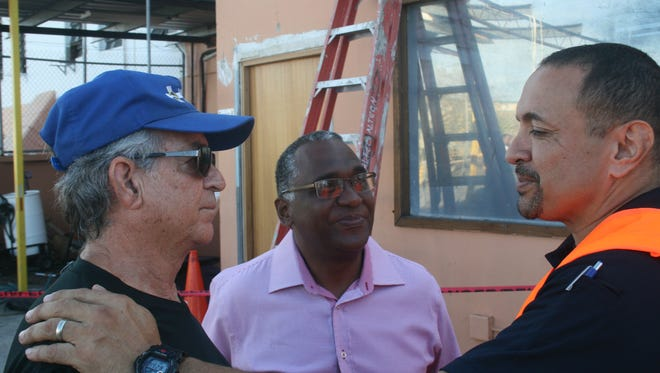 Titusville missionary Joe Hurston (left) discusses the logistics of distributing more than 60,000 pounds of aid sent by Remote Area Medical with Benjamin Puente Nelida Trujillo (center) and Riccardo Sanabria (right) on Saturday Oct.  7 in Aguadilla, Puerto Rico.