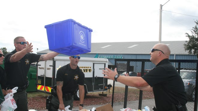 Martin County Sheriff's deputies lend a hand in unloading the donated food at the fairgrounds.