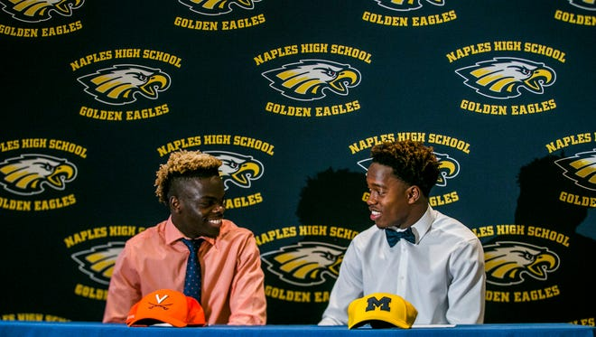 Sammy Faustin, right, and Wooby Theork sign with Michigan and Virginia, respectively, at Naples High School on Wednesday, Dec. 20, 2017.