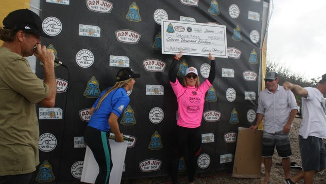Caroline Marks holds her prize after winning the Florida Pro surfing competition earlier this year.