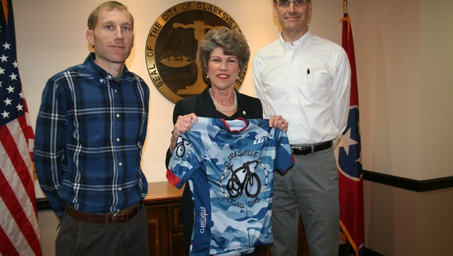 Clarksville Cycling Club members Lawrence Mize and Alex King present Mayor Kim McMillan with an official club riding jersey during a recent meeting at City Hall.