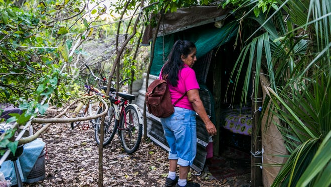 "Jesusita ""Susanna"" Rodriquez arrives at her camp at the end of the day in Immokalee on Wednesday, March 7, 2018. Rodriguez was left homeless after Hurricane Irma. The home she rented is uninhabitable because of extensive roof and water damage. She built a camp in the woods with scraps of wood and tarp and sleeps on a mattress she found on the street."