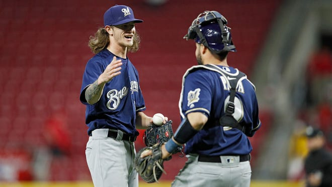 Brewers catcher Manny Pina congratulates reliever Josh Hader after Hader struck out eight Reds in 2 2/3 inning Monday night in Cincinnati.