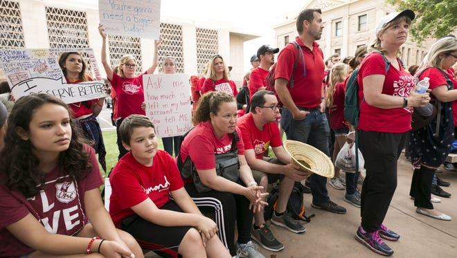 Teachers and other supporters listen during a press conference held by the Arizona Education Association and Arizona Educators United, during the fourth day of the Arizona teacher walkout at the Arizona state capitol in Phoenix on Tuesday, May 1, 2018. It was announced at the press conference that the teacher walkout will end Thursday if lawmakers pass the budget by Thursday.