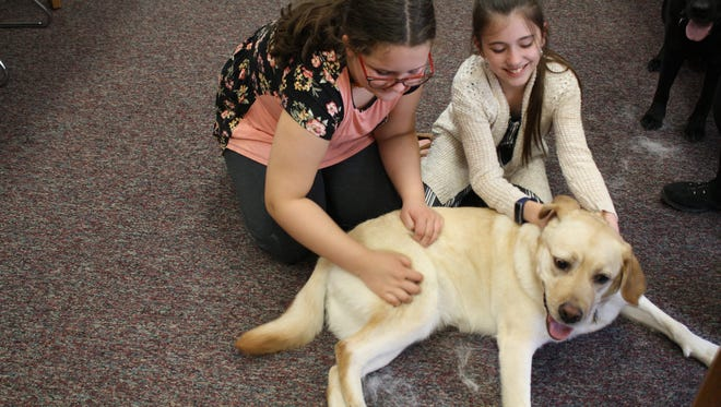 Fifth graders Anne Coleman, 10, and Hailey Smallacomb, 10, pet Gracie, a therapy dog at Windsor's Palmer Elementary School.