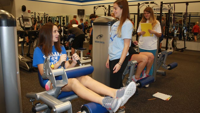 Fort Thomas residents and Highlands High School freshmen Sarah Ganote lifts her legs in a seated leg curl machine as she talks with Ramey Hensley inside the new fitness center.