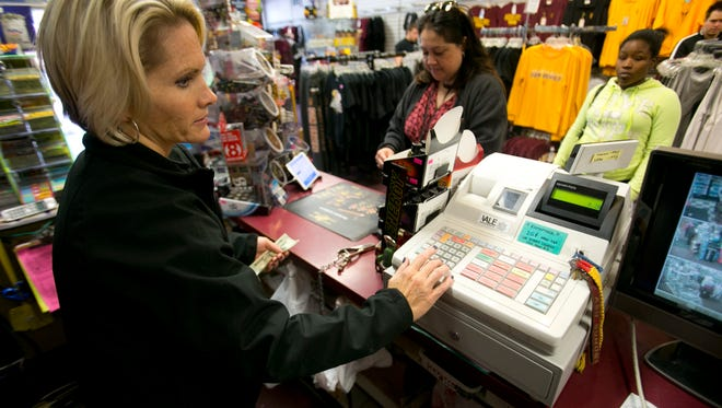 Manager Jessica Campbell works the cash register at Campus Corner on Mill Avenue in Tempe on Tuesday, December 10, 2013.