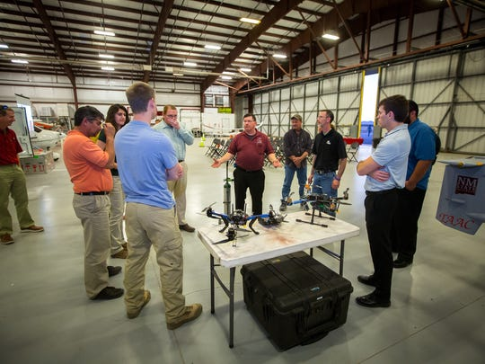 NMSU's Senior Security Manager Dennis Zaklan, center, talks to visitors during an open house inside the university's Physical Science Laboratory hangar at the Las Cruces Airport on March 17, 2016.