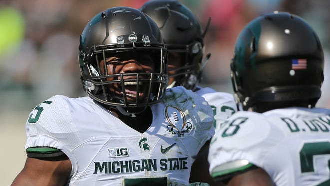 Michigan State's David Dowell, left, and Andrew Dowell celebrate after a interception in Saturday's spring game in East Lansing.