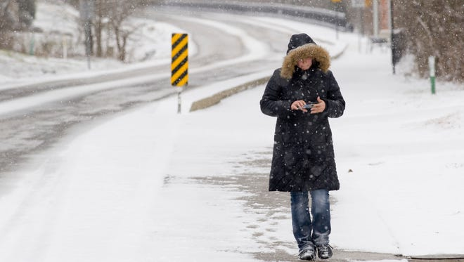 Bethany Rasche strolls through the snow along the Newburgh Rivertown Trail while playing a video game Thursday morning. The Tri-State Area received a heavy dusting of the white stuff for the first snowfall of the new year.