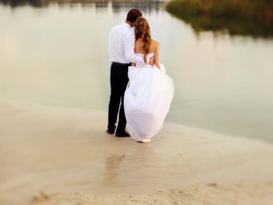 bride and groom standing on the edge of the beach