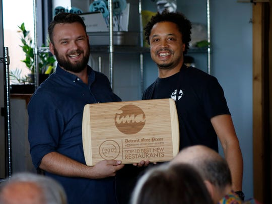 Mark Kurlyandchik, Detroit Free Press restaurant critic, left, presets an award to the head chef, Mike Ransom, right, during the Detroit Free Press/Metro Chevy Dealers Top 10 Takeover of the Ima, on Tuesday, July 27, 2017, in Detroit.
