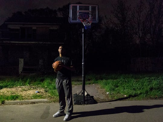 Michael Green stands under the same basketball hoop he was shot at when he was only 12 years old. Pictured on April 28, 2017, Green today is 19 and still plays ball at the same hoop near his Detroit home. Green is featured in Aftermath, a podcast about gunshot survivors.