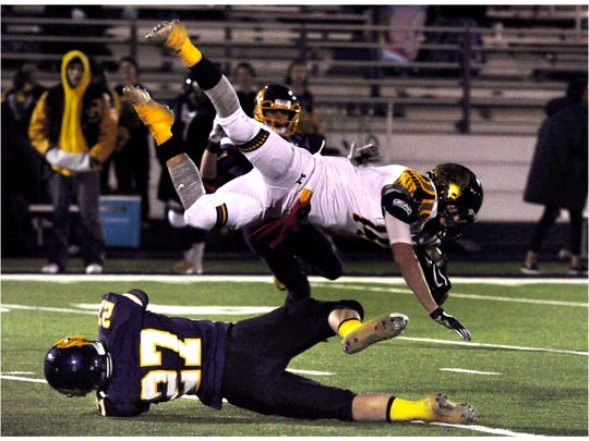Snyder High School wide receiver Nathan Kendrick flips into the air after being knocked over by Wylie High School defensive back Bailey Hicks during their game in 2017.