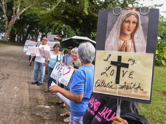 Members of the Catholic community gather near the gated driveway leading to the Archdiocese of Agana chancery, as the prepare to stage a protest in Hagatna, on Thursday, Feb. 16, 2017. The protest was to be held during a meeting between Roland Sondia and Vatican tribunal members at the chancery. Sondia previously announce that he was allegedly sexually assaulted by Archbishop Anthony Apuron in the 1970s when he served as an altar boy at an Agat church.