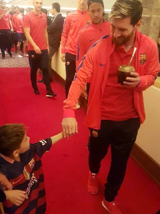 In this Tuesday, Dec. 13, 2016 photo released by The Supreme Committee for Delivery & Legacy, SC, Lionel Messi holds the hand of Murtaza Ahmady in Doha, Qatar. Murtaza made a special trip from Afghanistan to Qatar, where Messi was with his Barcelona teammates to play a friendly match against Al Ahli on Tuesday. (The Supreme Committee for Delivery & Legacy, SC via AP)