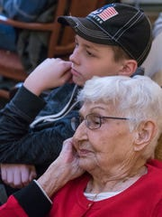 Lucy Grenier listens to Dr. Murray Howe with great-grandson Leo Tykoski, 13, who plays hockey with the Livonia Knights.