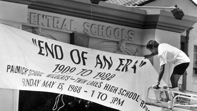"""Arnold Clark of Ferrin Signs hangs a banner in May 1988 announcing the """"End of an Era"""" party honoring the history of Palm Beach High School and Twin Lakes High School."""