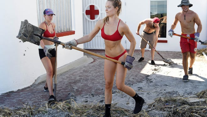 Jacksonville Beach lifeguard Cami Wight shovels sand with other current and former lifeguards Saturday, Oct. 8, 2016, as they help clean up after the Jacksonville Beach, Fla., lifeguard station took on sand and water during the storm surge that preceded Hurricane Matthew passing by the Jacksonville area. (Bob Self/The Florida Times-Union via AP)