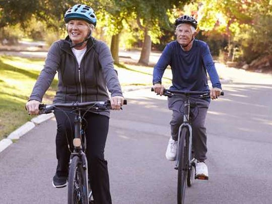 Elderly couple riding bikes together.
