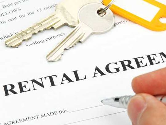 Pen in hand, signing a rental agreement.