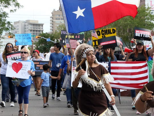 Marchers make their way down South El Paso Street before congregating at the base to the Paso Del Norte Port of Entry Saturday.