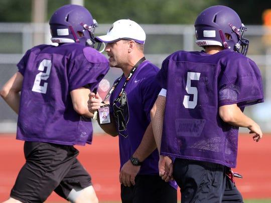 Monroe coach Chris Beagan works with his team during preseason football practice in 2013.