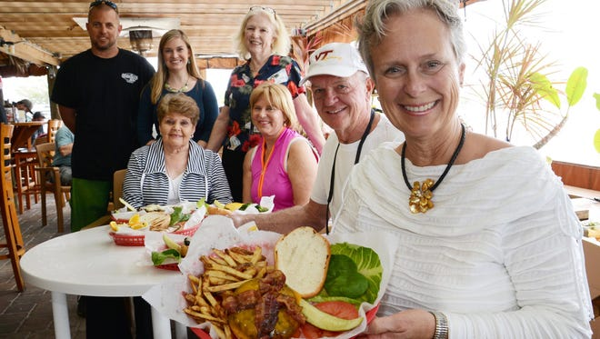 Michele and H.T. Everett, right. are the hosts of Melbourne Alumnae Panhellenic's fundraiser Cheeseburger in Paradise. The event will be catered by Cabana Shores. Others in the background are, from left, seated, Ann Anthony, Pat Honeywill. (standing) Josh Taylor, Marcia Meskiel-Macy and Anna Whittington.