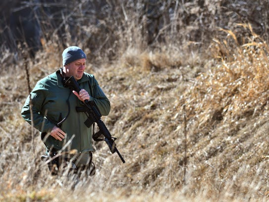 A law enforcement officer searches a wooded area for