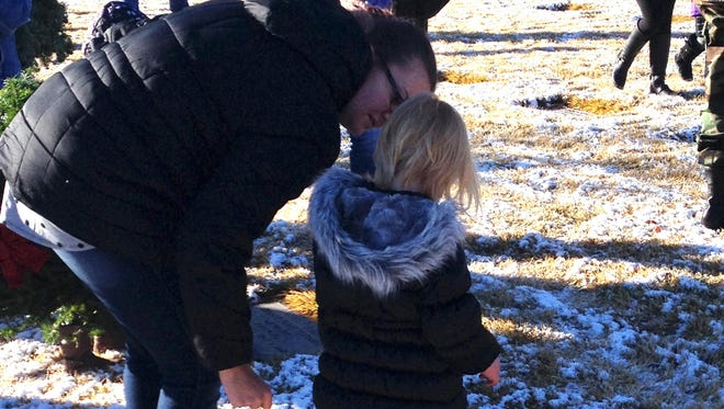 A mother and daughter laid a wreath at one of the graves at the Northern Nevada Veterans Memorial Cemetery. More than 1,500 participated in the ceremony.