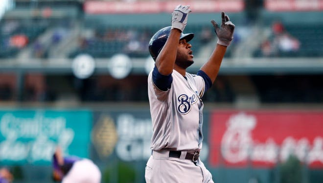 The Brewers' Lorenzo Cain celebrates as he heads to home plate after hitting a solo homer off the Rockies' German Marquez on Thursday night in Denver.