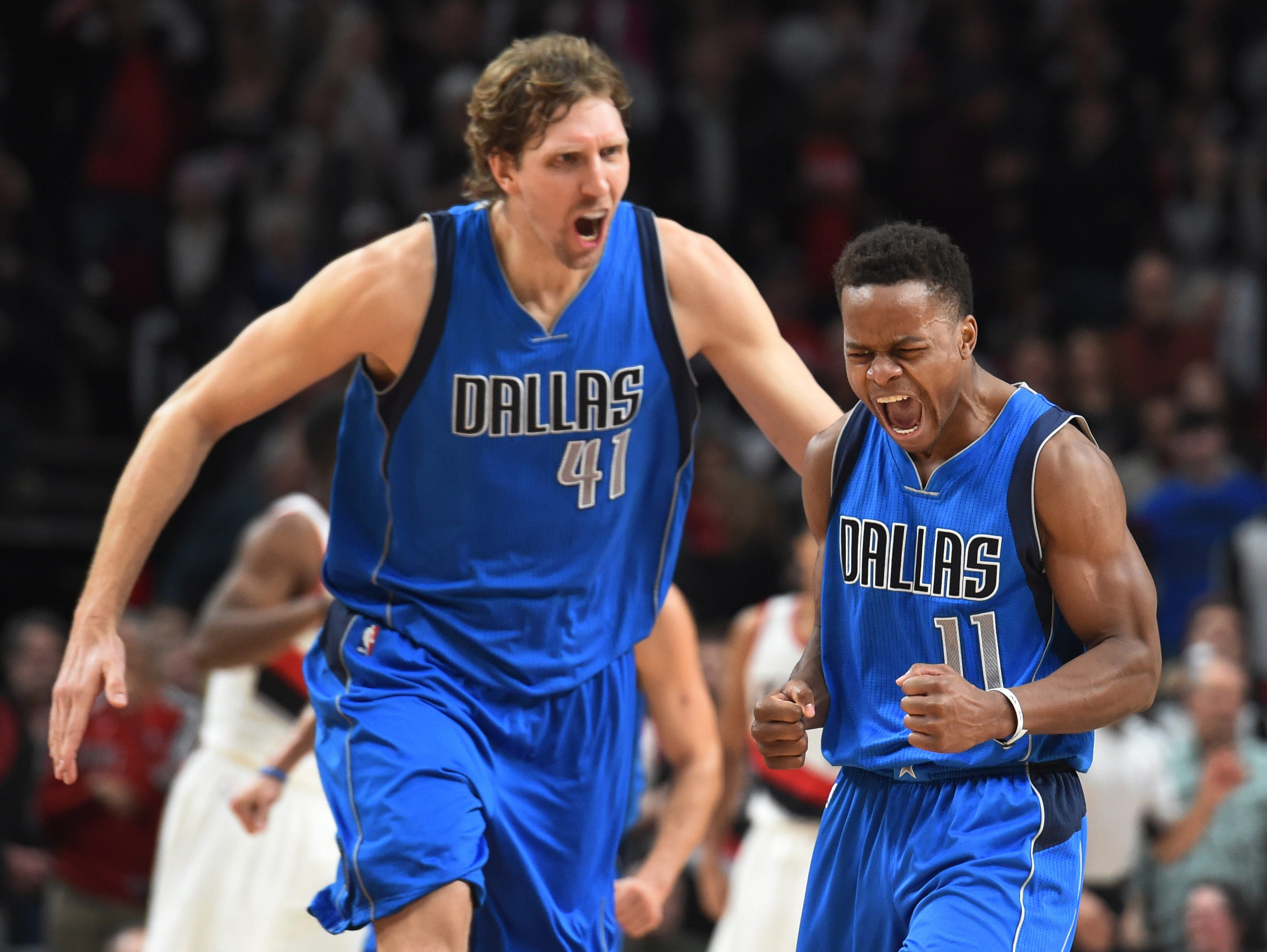 Dallas Mavericks guard Yogi Ferrell celebrates with forward Dirk Nowitzki after hitting a shot late in the fourth quarter of the game against the Portland Trail Blazers at the Moda Center. Dallas won the game 108-104.