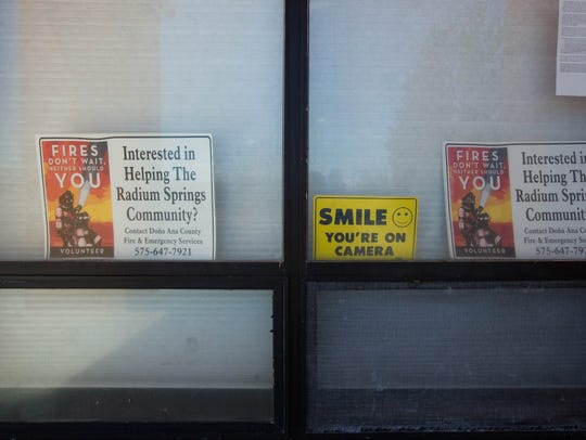 Signs in Radium Springs ask residents to consider becoming volunteer firefighters, inside the windows of the Radium Springs Fire Station, Friday August 24, 2018. The lack of volunteers has led the fire district to be downgraded.