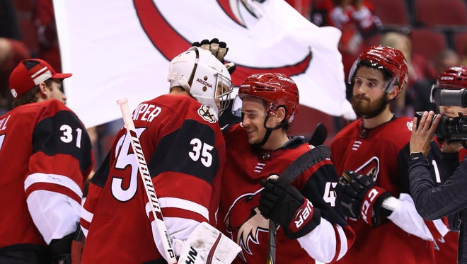 Mar 11, 2018: Arizona Coyotes goalie Darcy Kuemper (35) celebrates with teammate right wing Josh Archibald (45) after defeating the Vancouver Canucks in a 1-0 shutout at Gila River Arena.