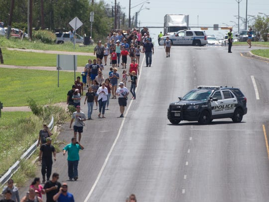 Spectators walk down Leopard Street to the Annaville Fire Station No. 1 as President Donald Trump's motorcade arrives for a briefing on Hurricane Harvey recovery efforts on Tuesday, Aug. 29, 2017.