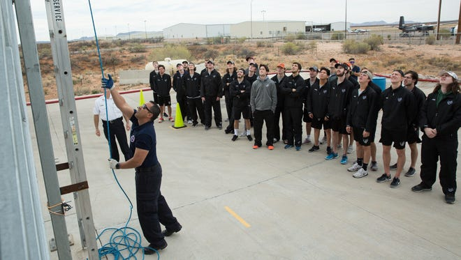 Las Cruces Fire Fighter Tony Aguilar, demonstrates the ladder drill for the El Paso Rhinos Hockey team, Saturday, February 18, 2017.