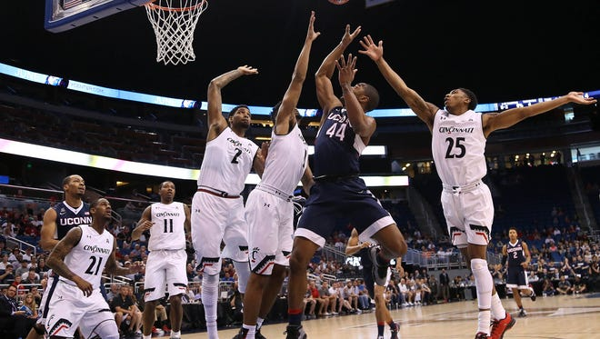 Connecticut Huskies guard Rodney Purvis (44) takes a shot as Cincinnati Bearcats forward Jacob Evans (1) and guard Kevin Johnson (25) defend in the first half during the AAC Tournament at the Amway Center.