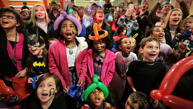 Families crowd under the clock tower at the Children's Museum of Memphis for a countdown during the New Year's at Noon: Superhero Spectacular. This year's event was so large, with an estimated 3,700 visitors to the museum, that organizers added a second countdown at 3 p.m. as well as gymnasts, costumed superheros, face painting and jugglers.