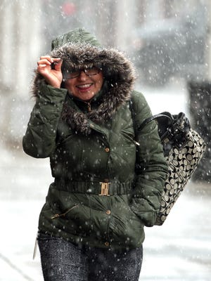 Luisa Rodriguez of Succasunna keeps her smile while braving the driving snow as the Northeast saw a storm on the first day of spring.